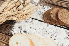 Un pacco di grano e papavero e farina sparsa e fette di pane sulle vecchie plance di legno Fotografia Stock Libera da Diritti