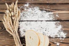 Un pacco di grano e papavero e farina sparsa e fette di pane sulle vecchie plance di legno Fotografie Stock