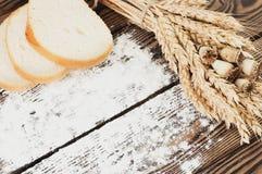 Un pacco di grano e papavero e farina sparsa e fette di pane sulle vecchie plance di legno Immagine Stock Libera da Diritti