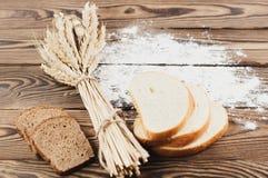 Un pacco di grano e papavero e farina sparsa e fette di pane sulle vecchie plance di legno Immagine Stock