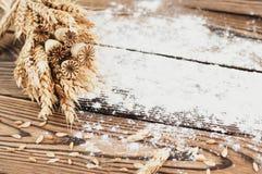 Un pacco di grano e papavero e farina sparsa sulle vecchie plance di legno Immagine Stock Libera da Diritti