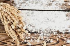 Un pacco di grano e papavero e farina sparsa sulle vecchie plance di legno Fotografia Stock