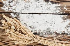 Un pacco di grano e papavero e farina sparsa sulle vecchie plance di legno Fotografie Stock Libere da Diritti