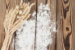 Un pacco di grano e papavero e farina sparsa sulle vecchie plance di legno Immagine Stock