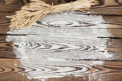 Un pacco di grano e papavero e farina sparsa sulle vecchie plance di legno Immagini Stock Libere da Diritti