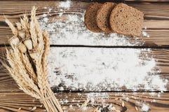 Un pacco di grano e papavero e farina sparsa e tre fette di pane sulle vecchie plance di legno Fotografia Stock Libera da Diritti