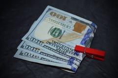 Un pacco di soldi con una molletta da bucato rossa Immagini Stock