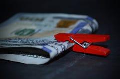 Un pacco di soldi con una molletta da bucato rossa Immagine Stock Libera da Diritti
