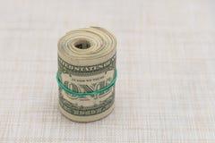 Un pacco di soldi torto in un pacco e legato con un elastico verde Immagini Stock Libere da Diritti