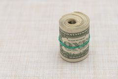 Un pacco di soldi torto in un pacco e legato con un elastico verde Fotografia Stock