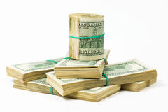 Un pacco torto di 100 banconote in dollari sta sui pacchetti dei dollari Immagine Stock