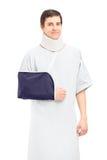 Un paciente masculino con una presentación quebrada del brazo y del cuello Foto de archivo libre de regalías