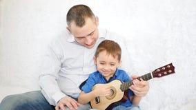 Un padre abraza a su hijo y le enseña a tocar la guitarra El concepto de una familia feliz metrajes