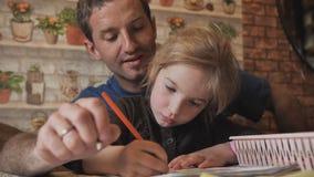 Un padre aiuta il suo tiraggio della figlia un disegno stock footage
