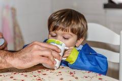 Un padre ayuda a su niño pequeño hermoso a beber el agua, mientras que ambos están en la cocina de su casa foto de archivo