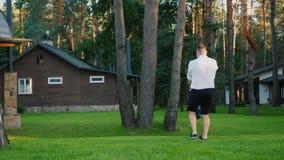 Un padre in buona salute gioca con il suo giovane figlio nel cortile della sua casa archivi video