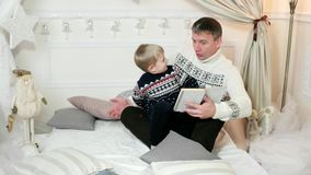 Un padre cariñoso lee un libro a su hijo, mientras que pasa el tiempo junto, familia que lee un libro, niño, almacen de metraje de vídeo