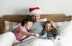 Un padre che racconta una storia di Natale ai suoi bambini immagini stock