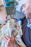 Un padre che si siede su una sedia in un'unità di cure intensive che tiene il suo ragazzo infantile malato Fotografia Stock Libera da Diritti