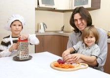 Un padre con dos muchachos en cocina Fotografía de archivo