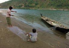 Un padre e un figlio che districano una rete da pesca prima della pesca andante nel fiume fotografie stock libere da diritti