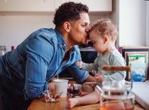 Un padre e un piccolo figlio del bambino che mangiano frutta e yogurt all'interno a casa fotografie stock libere da diritti
