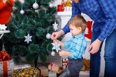 Un padre felice ed il suo giovane figlio decorano l'albero di Natale con i fiocchi di neve bianchi Immagini Stock