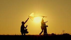 Un padre feliz con dos niños que juegan en el aire abierto que corre una cometa que vuela Silueta de la gente irreconocible en almacen de metraje de vídeo