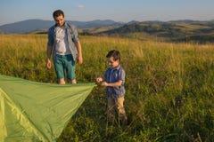 Un padre guarda a suo figlio come prova a mettere la tenda Immagine Stock