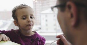 Un padre joven alimenta a un pequeño niño de una cuchara en un café metrajes
