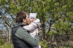 Un padre joven besa a una hija reci?n nacida, un paseo en el parque, pap? con un cuidado del amor de la dulzura del beb? fotos de archivo