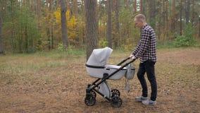 Un padre joven camina con un cochecito en el parque Un hombre con un bebé recién nacido metrajes