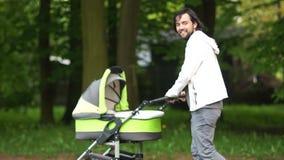 Un padre joven camina con un cochecito en el parque Un hombre con un bebé recién nacido paternity hippie Día del `s del padre metrajes