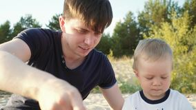 Un padre joven con un hijo joven en la playa que juega con el ` s de los niños juega almacen de metraje de vídeo