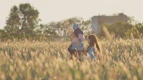 Un padre joven con una pequeña hija en sus hombros y su madre en un campo del trigo entre las espiguillas verdes adentro metrajes