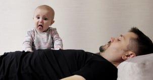 Un padre joven con una pequeña hija está mintiendo en el sofá metrajes