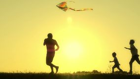 Un padre joven feliz y su funcionamiento de los niños en la puesta del sol en el verano y vuelan una cometa Silueta de una famili