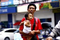 Un padre lleva a su niño mientras que camina en la calle Imagen de archivo