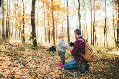 Un padre maturo e un figlio del bambino in una foresta di autunno, prendente le immagini con una macchina fotografica fotografia stock libera da diritti