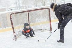 Un padre que juega en la pista de patinaje en invierno Foto de archivo