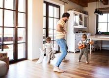Un padre y niños del niño que juegan dentro en casa imágenes de archivo libres de regalías