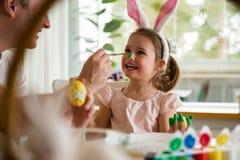 Un padre y una hija que celebran Pascua, huevos de pintura con el cepillo foto de archivo libre de regalías