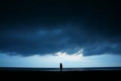 Un paesaggio del mare di sera con una siluetta della ragazza Fotografia Stock