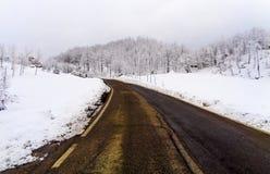 Un paesaggio della montagna con neve e la via Fotografia Stock Libera da Diritti