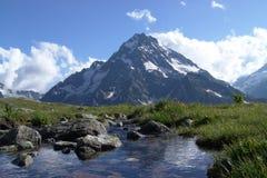 Un paesaggio della montagna con un picco e una corrente Fotografia Stock