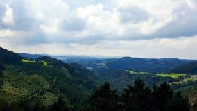 Un paesaggio delle alpi austriache con le nuvole e gli alberi scuri Immagini Stock Libere da Diritti