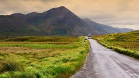 Un paesaggio irlandese scenico della natura con il bus turistico fotografie stock libere da diritti