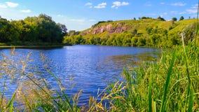 Un paesaggio pittoresco del fiume che fa una curvatura con un'alta riva Immagine Stock Libera da Diritti