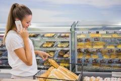 un pain de achat de femme dans l'étagère de pâtisseries Photographie stock libre de droits