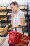 un pain de achat de femme dans l'étagère de pâtisseries Image stock